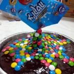 אח״כ מדביקים על קצה השיפוד בצמוד את השקית הרייקה בעזרת שוקולד מומס שכמעט התקשה